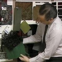Le couturier Jean-Claude Poitras regarde des tissus dans son atelier.