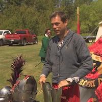 Un homme enfile une armure de chevalier.