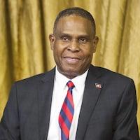 Un homme en complet veston et cravate porte une épinglette aux couleurs d'Haïti
