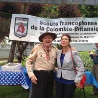 Un homme âgé avec un uniforme de scout et un chapeau brun sourit à pleines dents avec un bras sur les épaules d'une dame aux cheveux courts bruns avec un veston gris.