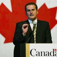 Jean Lapierre parle au micro devant un lutrin. Un immense drapeau du Canada se trouve derrière lui.