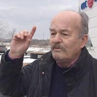 Jean-Marie Nadeau lève l'index lors d'une entrevue devant les locaux de Radio-Canada.