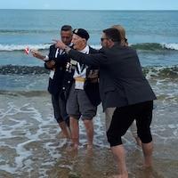 L'ancien combattant Jean Trempe, entouré de quelques personnes, a les pieds dans l'eau à la plage Juno.