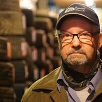 Jean-Yves Viel portant une casquette dans un entrepôt de pneus.