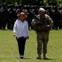 Elle est accompagnée d'un soldat avec en arrière-plan une rangée de militaire.