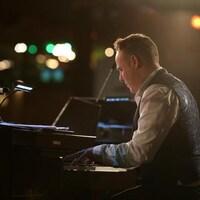 Photographié de profil, le musicien joue du piano sur scène.