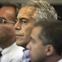 Un homme aux cheveux gris, entouré d'autres hommes, subit son procès.