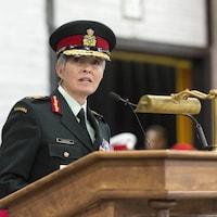 La générale Carignan prononçant un discours sur une tribune lors d'une cérémonie militaire.