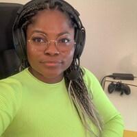 Portrait d'une femme racisée avec un casque de jeux vidéo qui regarde la caméra.