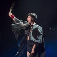 De profil, un homme chante. Il tient à bout de bras une longue plume. Il porte une cape faite d'un tissu transparent.