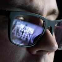 Reflet d'une image de casino virtuel dans les lunettes d'un homme.