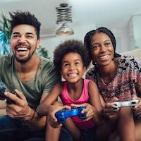 Un homme, une femme et un enfant jouent à un jeu vidéo en famille avec enthousiasme dans un salon.