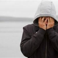 Un jeune portant un capuchon cache son visage dans ses mains