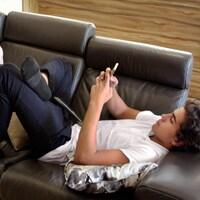 Des adolescents sur un sofa regardent des appareils électroniques.
