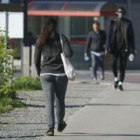 Des jeunes adultes marchent sur un trottoir.