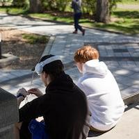 Deux ados de dos, assis dans les marches en béton du parc Morgan.