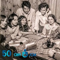 Des gens se trouve autour d'une table sur une photo en noir et blanc.