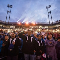 Des participants à la cérémonie d'ouverture des Jeux autochtones chantent et saluent pendant l'« Ô Canada ».