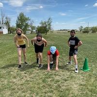 Quatre jeunes se prépare à courir en plein-air.