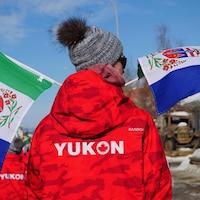 Un athlète porte un manteau aux couleurs du Yukon lors d'un défilé  à Whitehorse en mars 2020.