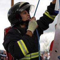 Une pompière brésilienne Gabriela Oliveira participe aux Jeux mondiaux des policiers et pompiers à Belfast en Irlande du Nord en 2013.