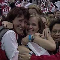 Trois femmes se prennent dans leur bras en souriant.