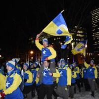 Des membres de la délégation de l'Est-du-Québec portent fièrement le drapeau qui les représente.