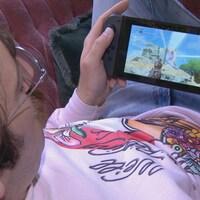 Une personne joue à un jeu vidéo qu'il tient entre ses mains.