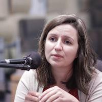 Une femme parlant à un micro dans un studio.