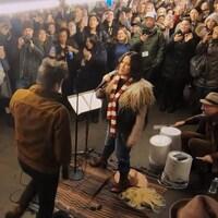 Une foule entassée regarde et filme avec des téléphones intelligents la prestation d'un duo qui chante dans un métro.