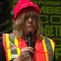 Joanne raconte son histoire devant une cinquantaine de travailleurs. Elle porte un casque de sécurité sur la tête.