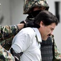 Deux soldats flanquent Joaquin El Chapo Guzman qui apparaît en chemise blanche, la tête légèrement inclinée.