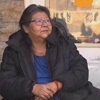 Une femme assise devant une résidence.
