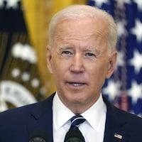 Joe Biden parle dans un micro devant un drapeau américain.