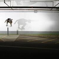 Un homme saute par-dessus une poutre d'environ un mètre de haut avec sa planche à roulettes.