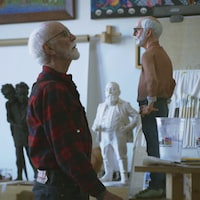 Joe Fafard, l'artiste face à une sculpture représentant son portrait.