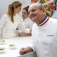 Joël Robuchon, accoudé à un comptoir, dans une cuisine.