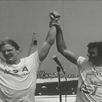 John Kinsella célèbre sa victoire les bras levés en l'air accompagnés d'autres participants sur la tribune de Roberval. En arrière-plan, le public massé dans les gradins sur le bord du lac St-Jean.