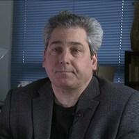 M. Lawford est assis à son bureau et s'adresse à la caméra.