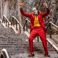 Un homme déguisé en clown est debout dans un escalier, les bras en l'air.