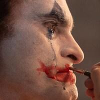 Un homme applique du maquillage de clown sur son visage.