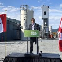 Un homme debout devant une tribune à l'extérieur d'une usine. Il est entouré de deux drapeaux canadiens.