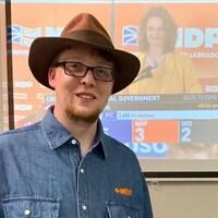 Jordan Brown devant un téléviseur qui diffuse la soirée électorale du 19 mai 2019, à Terre-Neuve-et-Labrador.