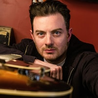 Un portrait du musicien, le bras appuyé sur une guitare posée à plat.
