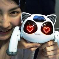 Une fillette posant avec un robot à la forme d'un chat avec des coeurs illuminés en guise de yeux.