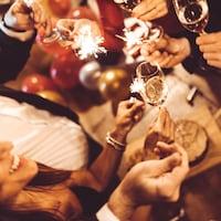 Des gens célèbrent le jour de l'An avec des petits artifices et des coupes de champagne.