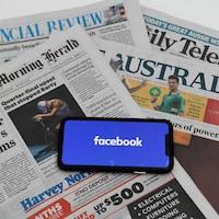 Des journaux avec un téléphone sur lequel on voit le logo de Facebook.