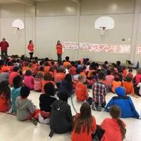 Des élèves portant un chandail orange, pour la plupart, sont assis dans un gymnase et écoutent des adultes, debout, devant eux. (archives)