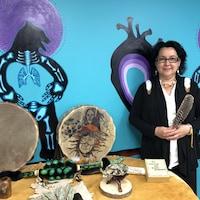 Une femme tient une plume devant des éléments autochtones.