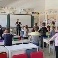 Judith Goulet fait un mouvement de yoga devant sa classe. Les élèves l'imitent.